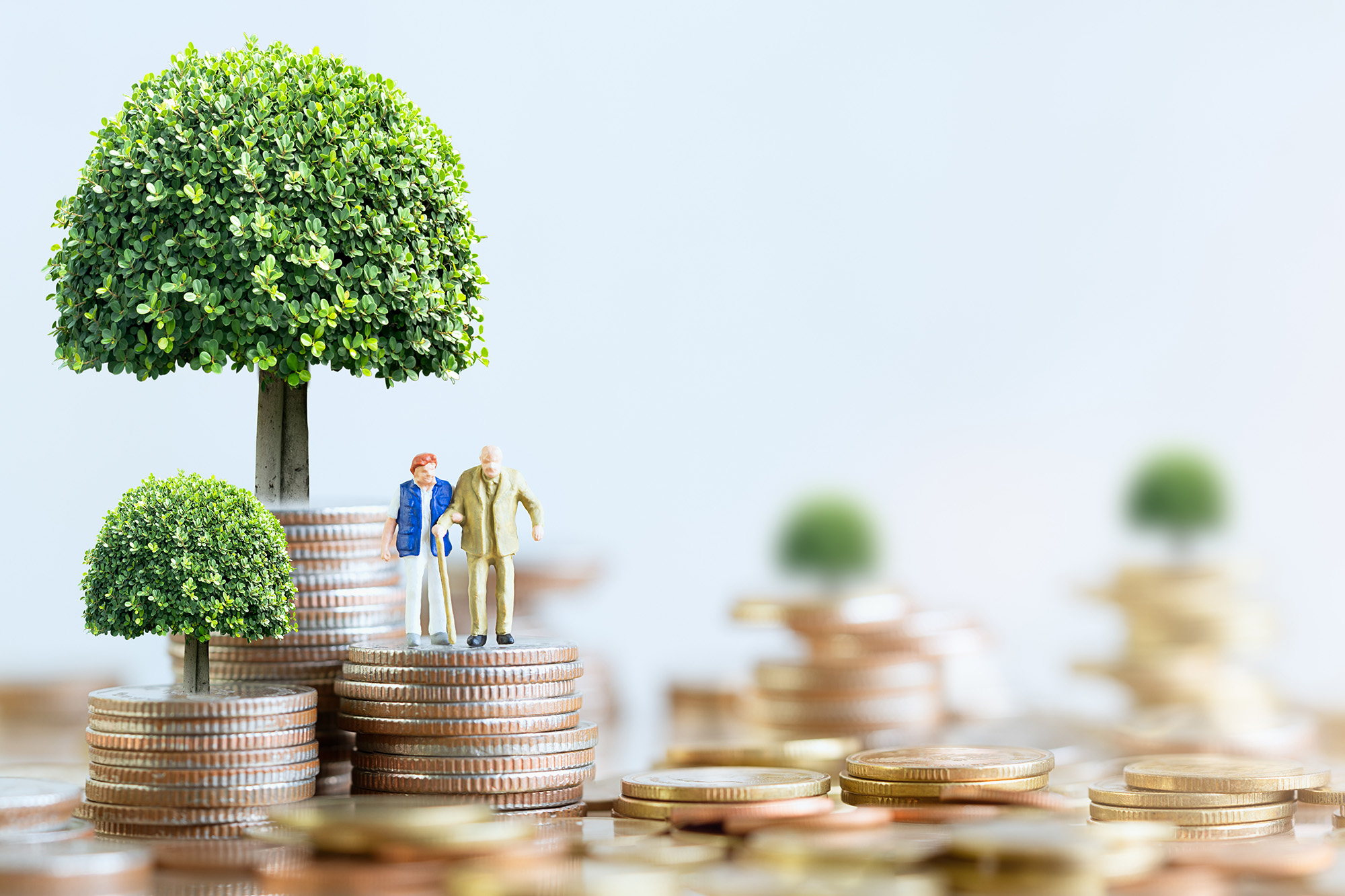 Miniature people: Elderly people sitting on coins stack. social
